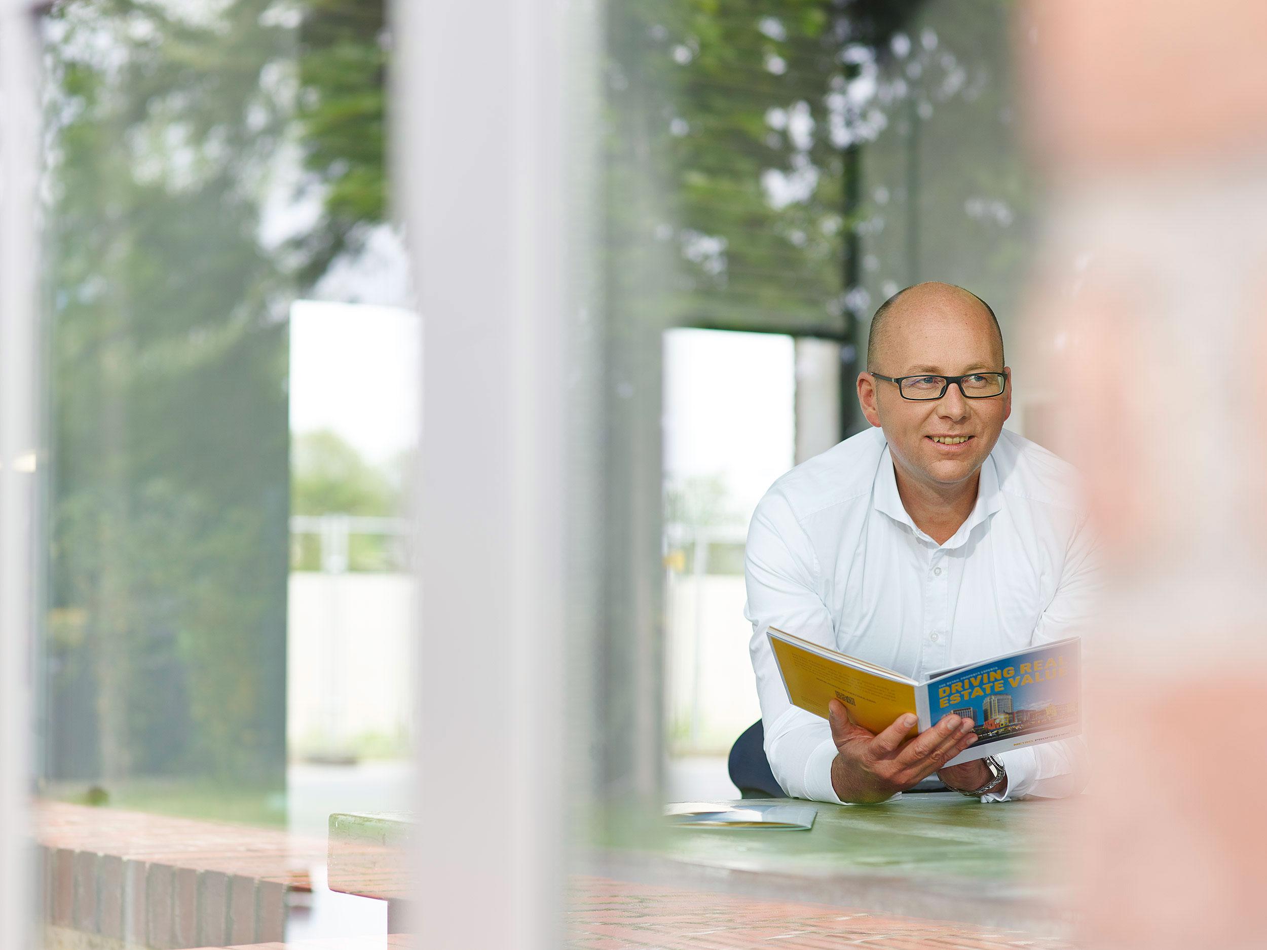 Mann mit halbglatte in weißem Hemd lacht, Broschüre in der Hand, Blick durchs Fenster in einen großen Raum.
