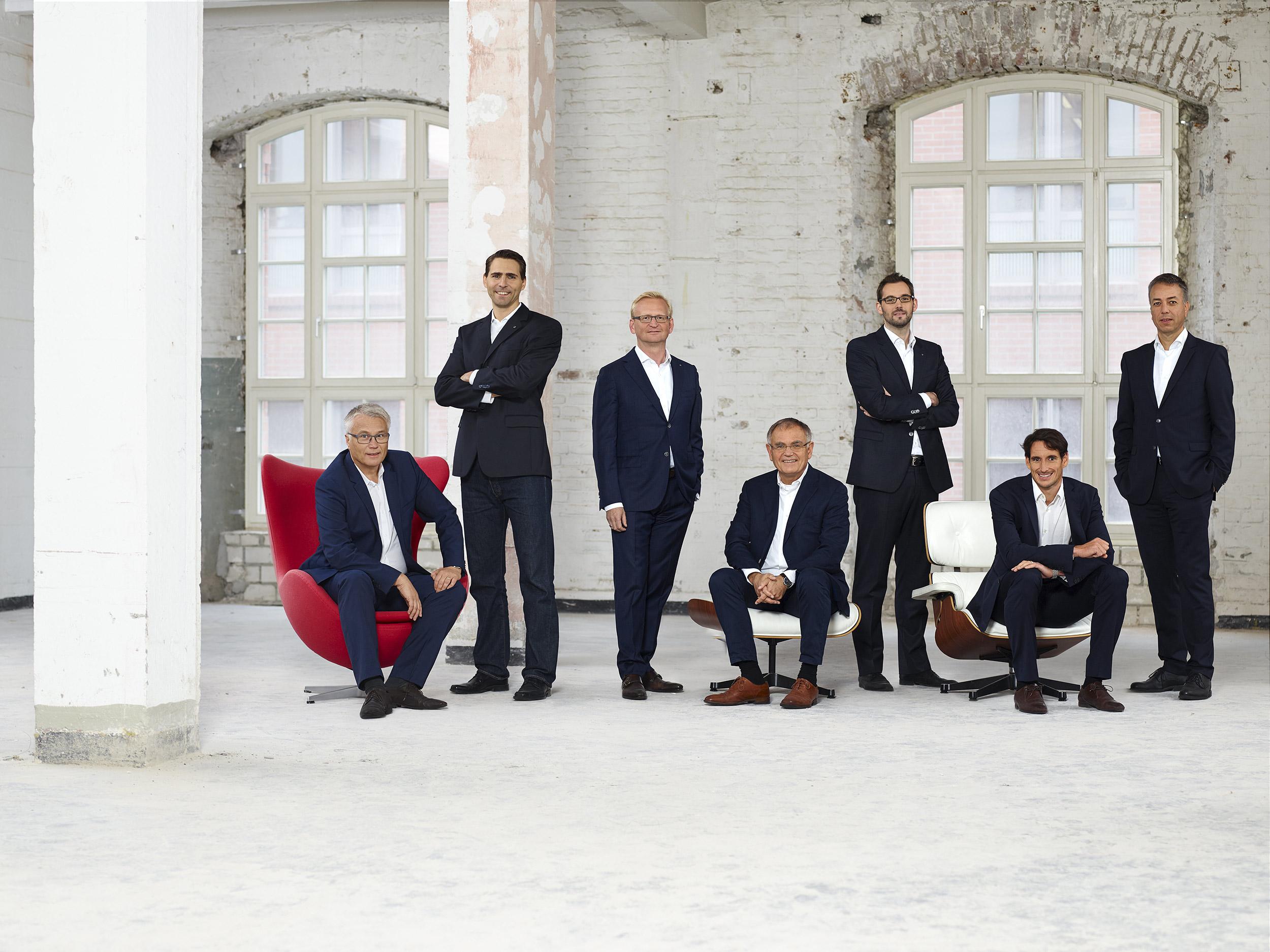 Gruppe von sieben Herren unterschiedlichen Alters und dunklen Anzügen in einem Rohbau Industieloft. Einer sitzt in einem roten Sessel einer auf einem weißen Hocker und einer in einem weißen Lounge Chair. Die anderen 4 stehen. Gruppe arrangiert im Raum verteilt.