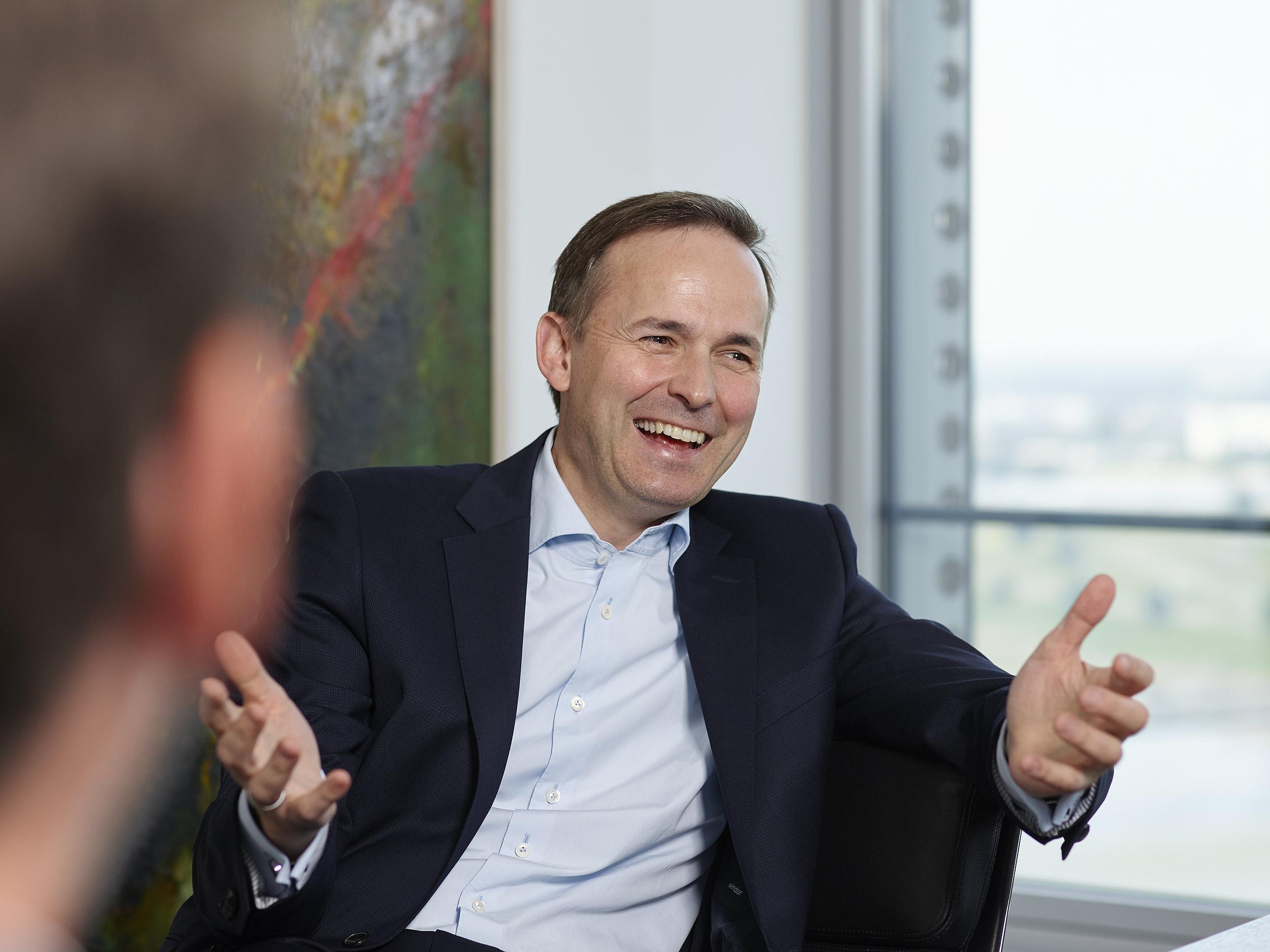 Mann in Hemd und Anzug sitz am Tisch vor Fenster und spricht, gestikuliert mit den Händen, lacht