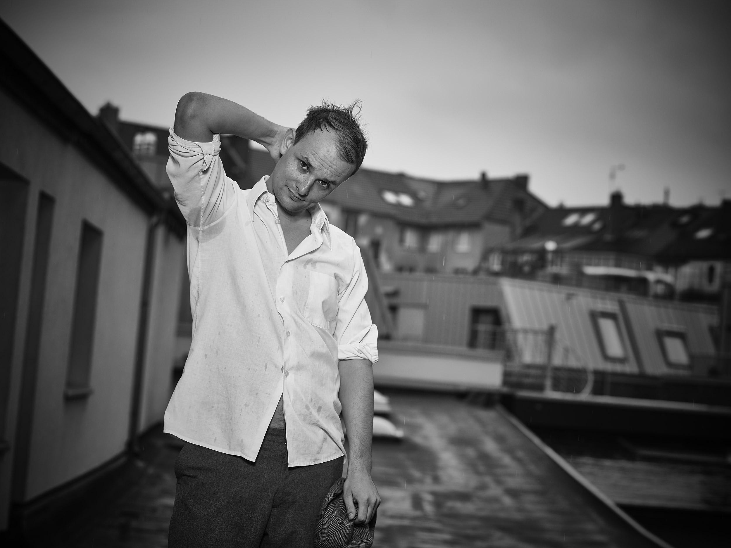 Junger Mann, ca. 30, steht im Regen dreckig auf einem Hinterhofdach. Porträt in schwarz weiß. Halbkörper. Mann guckt komisch aus dem Bild. Regen auf einem Dach im Hintergrund. Er trägt ein weisses Hemd. Man sieht Schweißflecken unter den Armen.