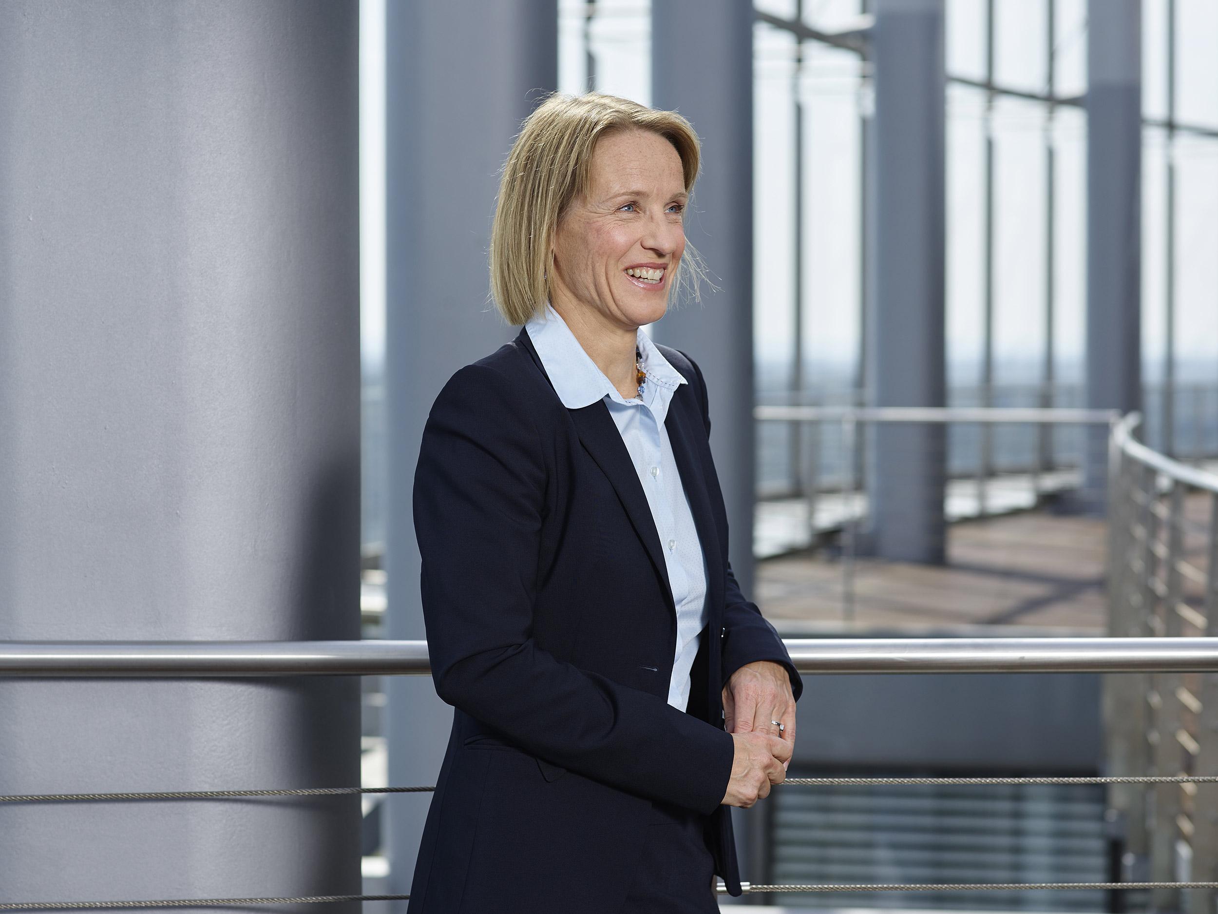 Blonde Frau in heller Bluse und dunklen Anzug steht an einem Geländer und lacht zur Seite auf einer Dachterrasse