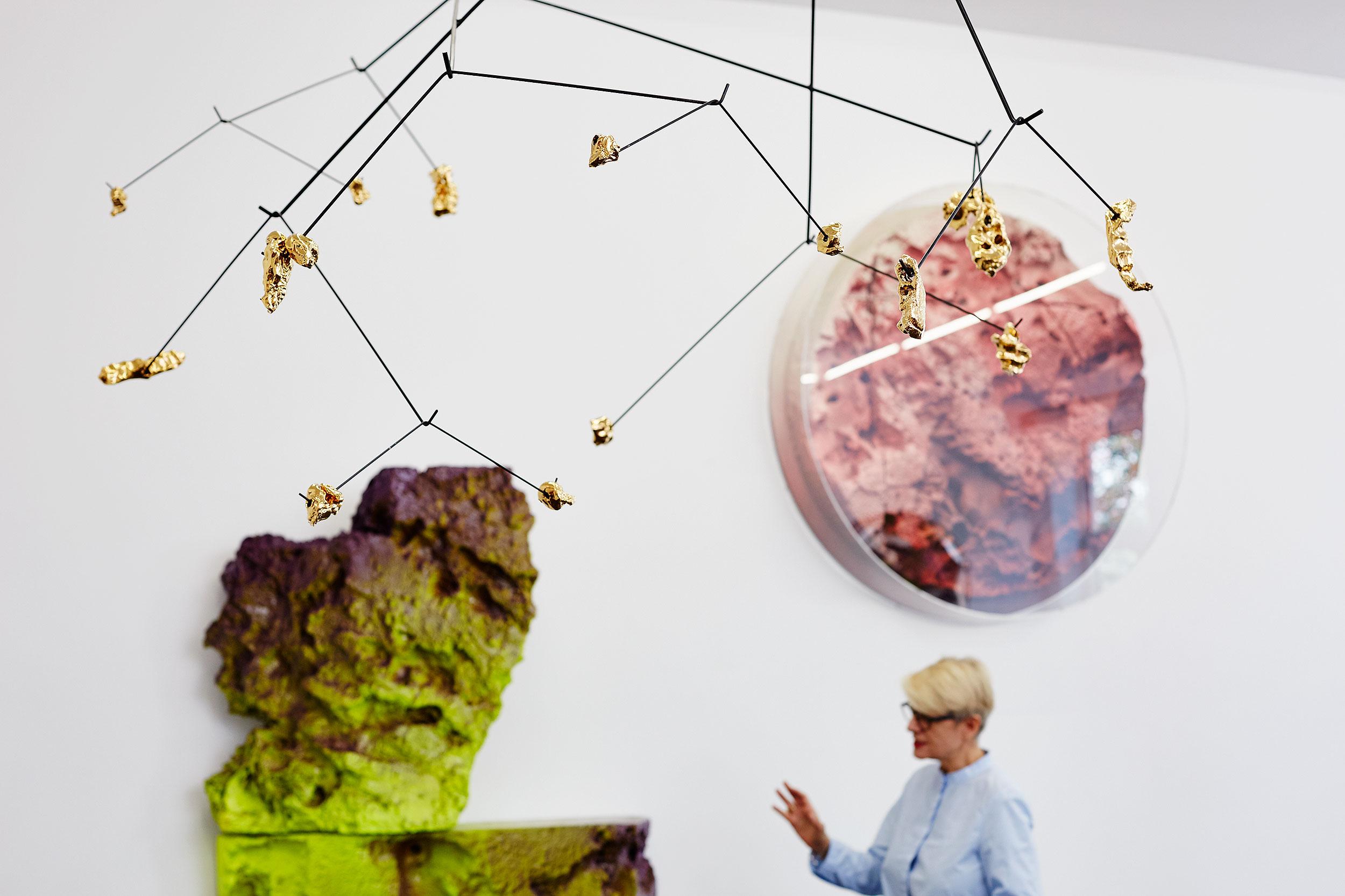 Kunst im Raum mit unscharfer blonder Dame im Hintergrund. Im Vordergrund Astähnliches schwarzes Drahtgestell von der Decke mit goldenen Seinen im Hintergrund grünbraune Steinskulptur und rundes rot-lila-skulpturales Bild an der Wand. darunter steht eine blonde Frau und gestikuliert.
