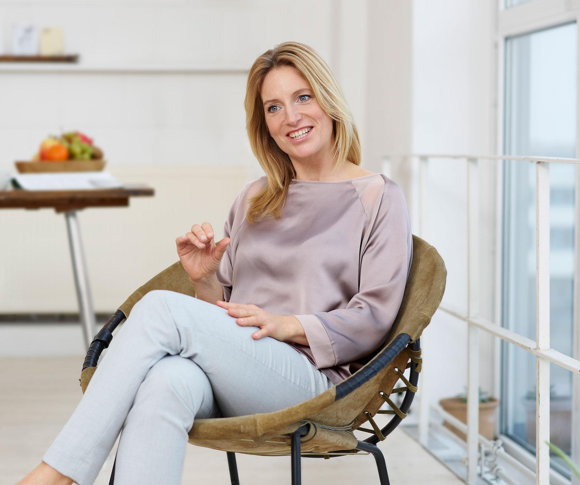 Anzeige für Centrum Darmflora, Gesundheitsexpertin mit blonden langen Haaren in Interviewsituation in braunem Ledersessel in einer hellen Location. Sie erklärt etwas im Hintergrund ist ein Tisch mit Obstschale zu sehen