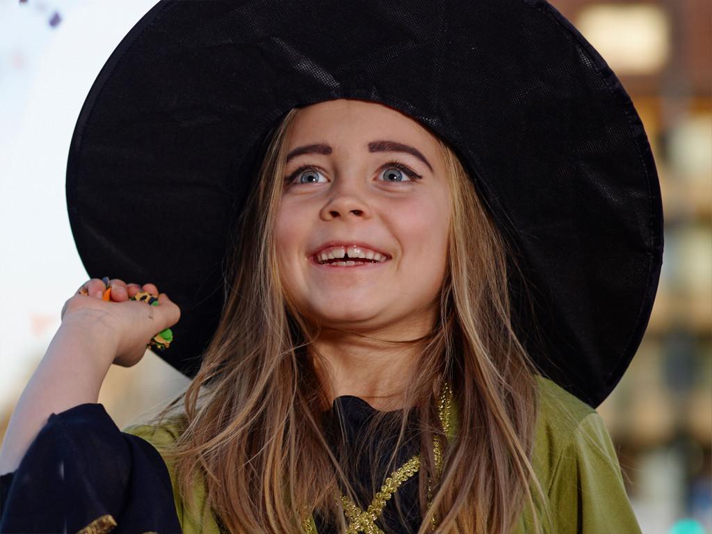Junges Mädchen mit schwarz-grünem Hexenkostüm steht auf der Straße in der Dämmerung und wirft Konfetti.