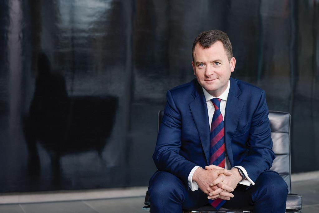 Mann, um die 50, sitzt auf einem Barcelona Chair, schwarzes Leder, vor einer schwarzen Wand, Halbkörperportrait. Der Mann trägt einen dunkelblauen Anzug und eine Blau-rot gestreifte Krawatte. er hat kurzes hellbraunes Haar und lächelt leicht in die Kamera.